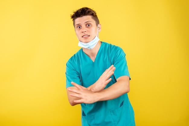Вид спереди молодой мужчина-врач в медицинском костюме со стерильной маской на желтом фоне