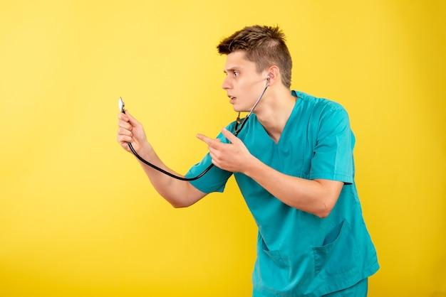노란색 배경에 청진 의료 소송에서 전면보기 젊은 남성 의사