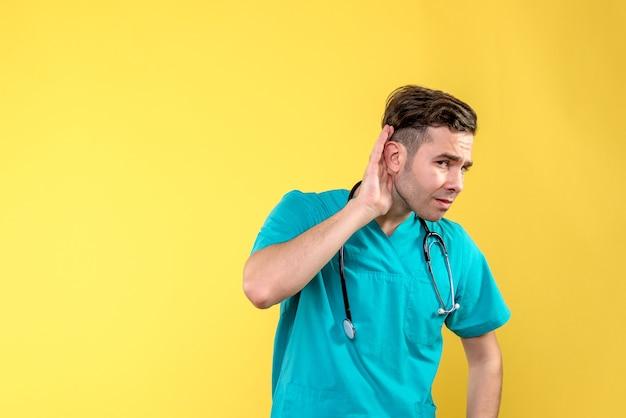Vista frontale del giovane medico maschio che ascolta sulla parete gialla