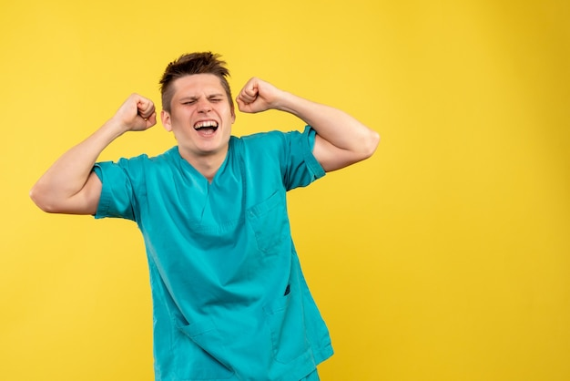 Front view young male doctor in medical suit emotionally rejoicing on yellow background