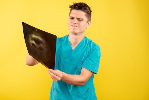 Vista frontale giovane medico maschio in tuta medica tenendo i raggi x su sfondo giallo Foto Gratuite
