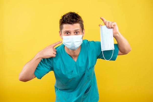 Giovane medico maschio di vista frontale in vestito medico e maschera sterile che tiene altra maschera su colore giallo