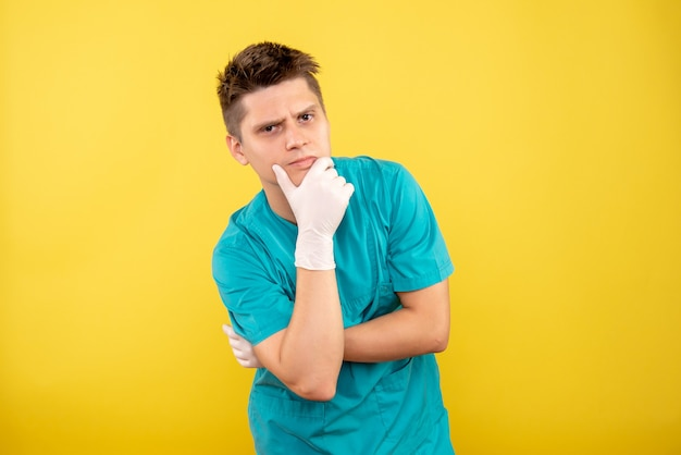 Front view young male doctor in medical suit with gloves thinking on yellow background