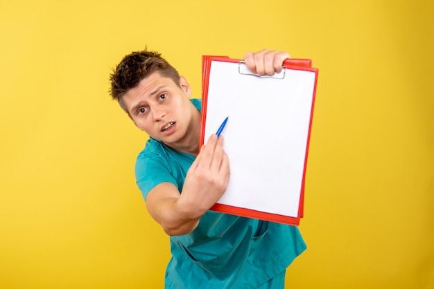Front view young male doctor in medical suit with note and analysis on a yellow background