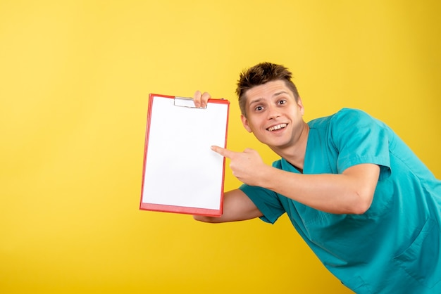 Front view young male doctor in medical suit with note and analysis on yellow background