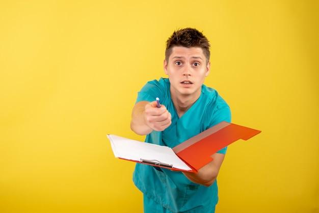 Vista frontale giovane medico maschio in tuta medica con note su sfondo giallo