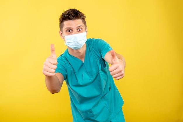 Vista frontale giovane medico maschio in tuta medica con maschera sterile su sfondo giallo