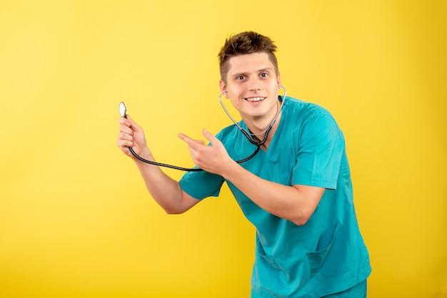 Giovane medico maschio di vista frontale in vestito medico con lo stetoscopio su priorità bassa gialla