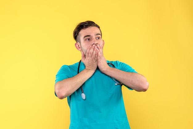 Vista frontale del giovane medico maschio scioccato sulla parete gialla