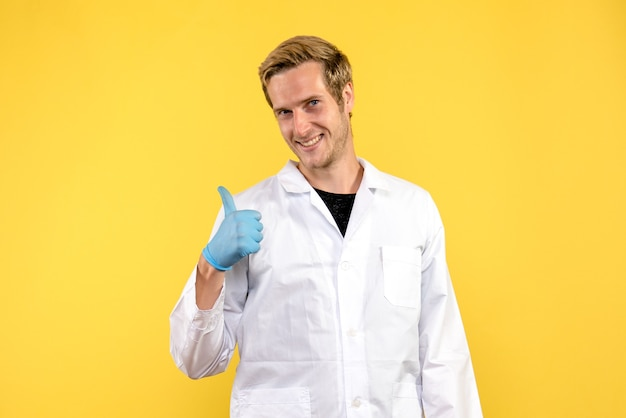 Front view young male doctor smiling on a yellow background human covid medic pandemic