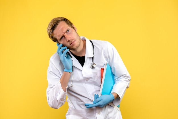 Front view young male doctor talking on phone on yellow background virus health medic human