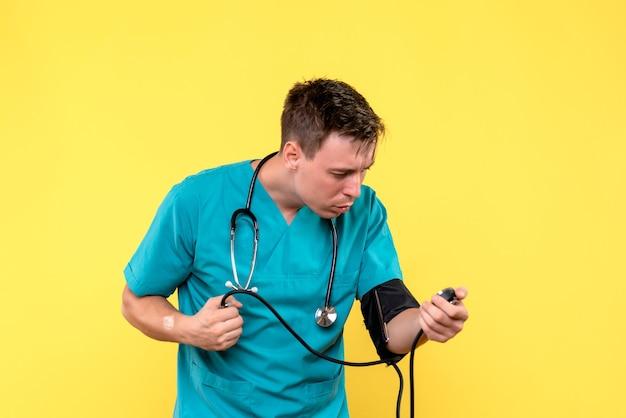 Vista frontale del giovane medico maschio utilizzando il tonometro sulla parete gialla