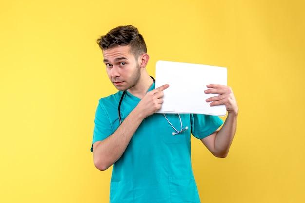 Vista frontale del giovane medico maschio con documenti sul muro giallo chiaro