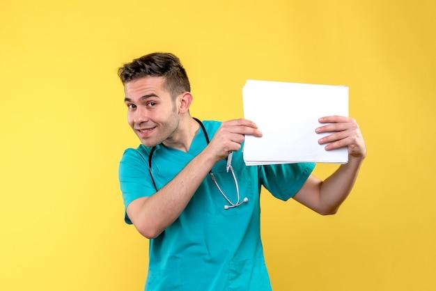 Vista frontale del giovane medico maschio con documenti sulla parete gialla