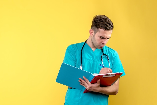 Front view of young male doctor writing notes on yellow wall