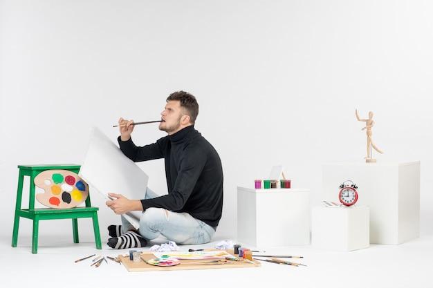 正面図白い壁にタッセル付きの若い男性のデッサン絵画色の仕事展示画像アートデッサンアーティストペイント