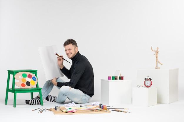 正面図白い壁にタッセルで絵を描く若い男性アートカラー絵の具描画アーティスト
