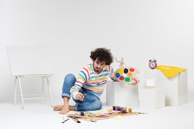Front view of young male drawing paintings on white wall