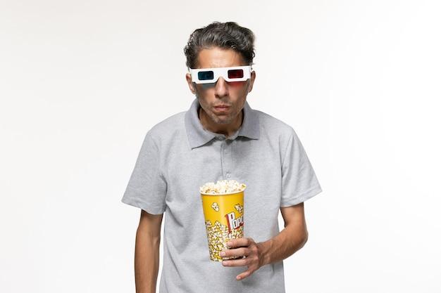 Giovane maschio di vista frontale che mangia popcorn in occhiali da sole d su superficie bianca chiara