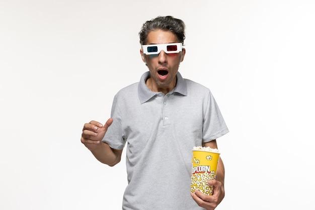 Giovane maschio di vista frontale che mangia popcorn in occhiali da sole d guardando film sulla superficie bianca chiara