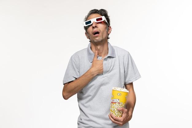 Giovane maschio di vista frontale che mangia popcorn in occhiali da sole d guardando film su superficie bianca