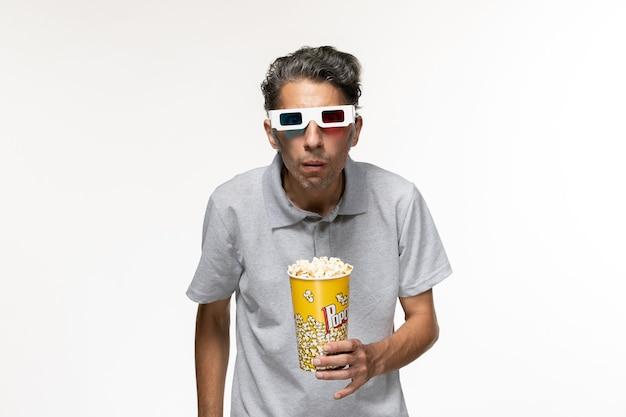 Giovane maschio di vista frontale che mangia popcorn in occhiali da sole d sullo scrittorio bianco