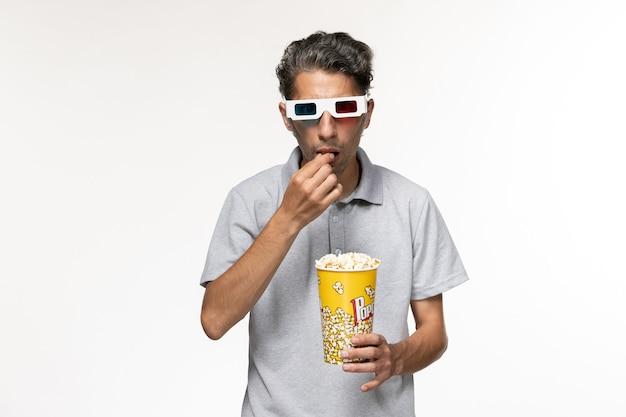 Giovane maschio di vista frontale che mangia popcorn in occhiali da sole d su superficie bianca