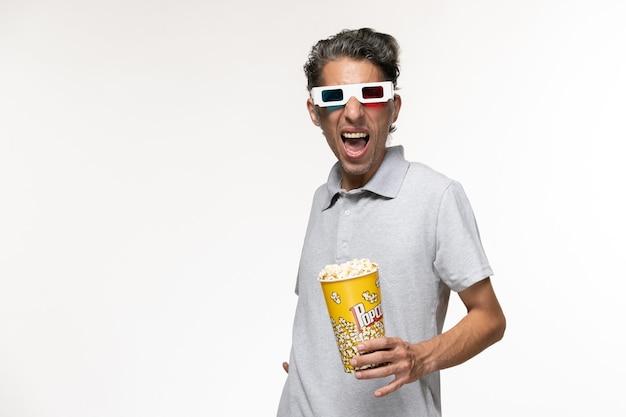 正面図白い表面にdサングラスでポップコーンを食べる若い男性