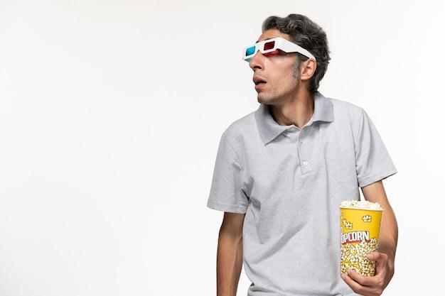 Giovane maschio di vista frontale che mangia popcorn e che guarda film in occhiali da sole d su una superficie bianca