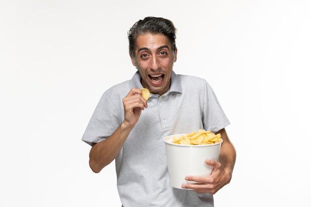 감자 칩을 먹고 밝은 흰색 표면에 웃고 전면보기 젊은 남성