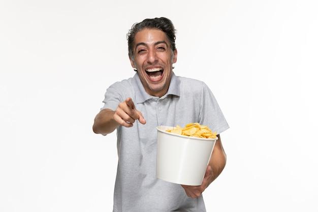 전면보기 젊은 남성 감자 칩을 먹고 흰색 표면에 크게 웃고