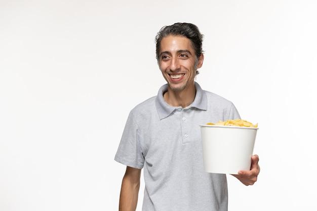 감자 칩을 먹고 흰색 표면에 웃는 전면보기 젊은 남성