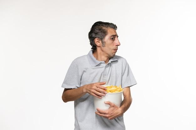 흰색 표면에 영화를보고 감자 칩을 먹는 전면보기 젊은 남성