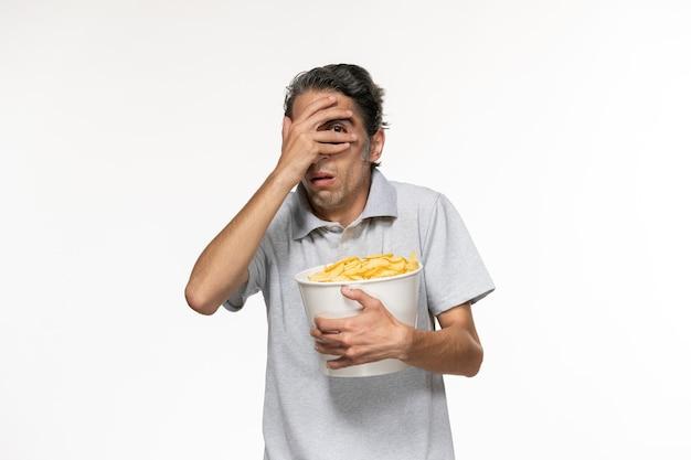 밝은 흰색 표면에 영화를보고 감자 칩을 먹는 전면보기 젊은 남성