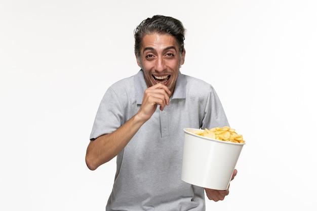 흰색 표면에 웃 고 감자 칩을 먹는 전면보기 젊은 남성