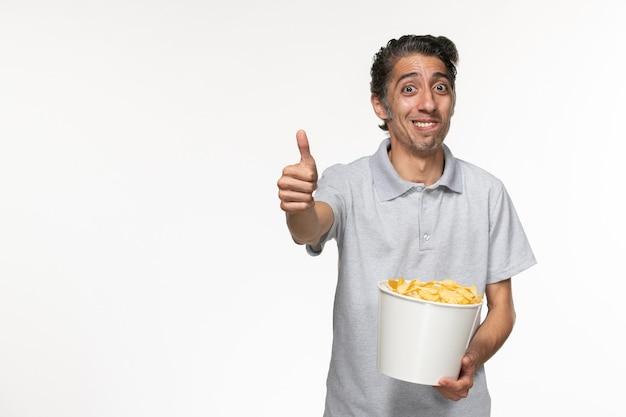 밝은 흰색 표면에 감자 칩을 먹는 전면보기 젊은 남성