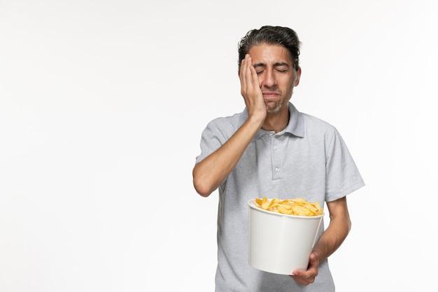 흰색 책상에 감자 칩을 먹는 전면보기 젊은 남성
