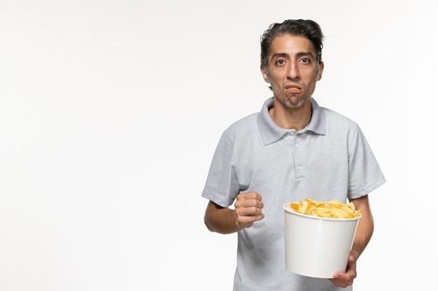 흰색 표면에 감자 칩을 먹는 전면보기 젊은 남성