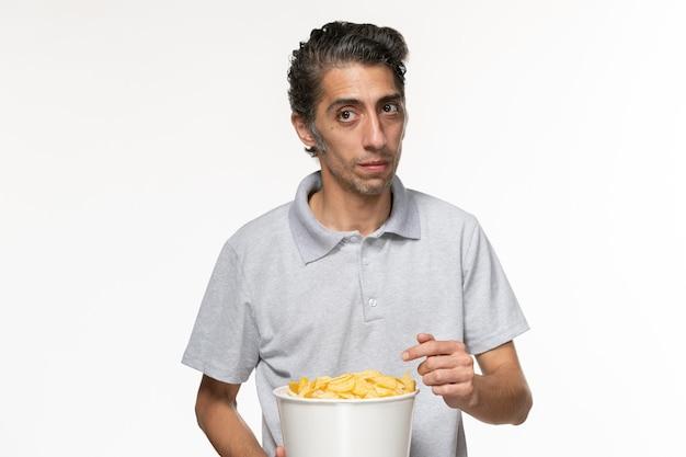 Вид спереди молодой самец ест картофельные чипсы на белой поверхности