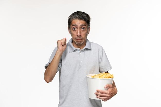 Вид спереди молодой мужчина ест картофельные чипсы, смотрит фильм на светлой белой поверхности