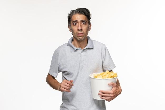 Вид спереди молодой мужчина ест картофельные чипсы, смотрит фильм на белой поверхности