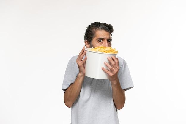 Giovane maschio di vista frontale che mangia patatine fritte che guarda film sullo scrittorio bianco