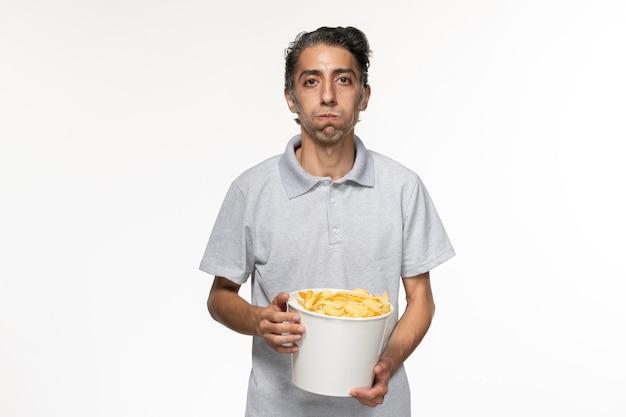 Giovane maschio di vista frontale che mangia patatine fritte sulla superficie bianca
