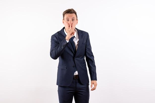 Vista frontale giovane maschio in elegante abito classico che chiede di tacere su sfondo bianco