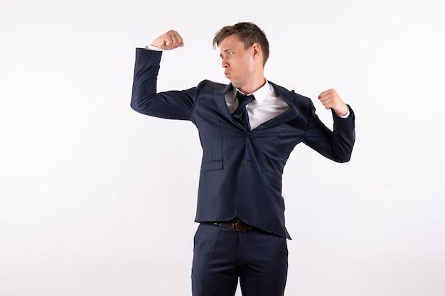 Giovane maschio di vista frontale che flette nel classico vestito rigoroso su sfondo bianco emozioni umano maschio vestito moda modello