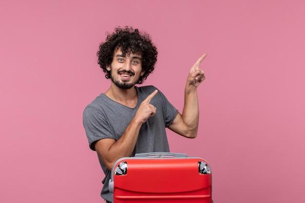 분홍색 공간에 웃고 휴가를 준비하는 전면보기 젊은 남성
