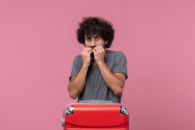 Vista frontale giovane maschio che si prepara per le vacanze ma spaventato sullo spazio rosa pink