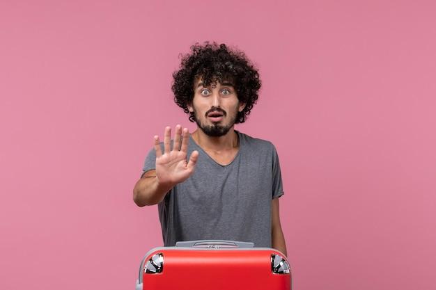 Giovane maschio di vista frontale che si prepara per la vacanza con la borsa sullo spazio rosa