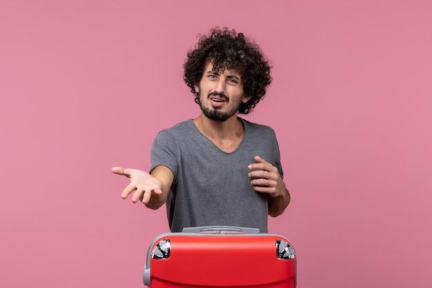 Vista frontale giovane maschio che si prepara per le vacanze con espressione confusa sullo spazio rosa