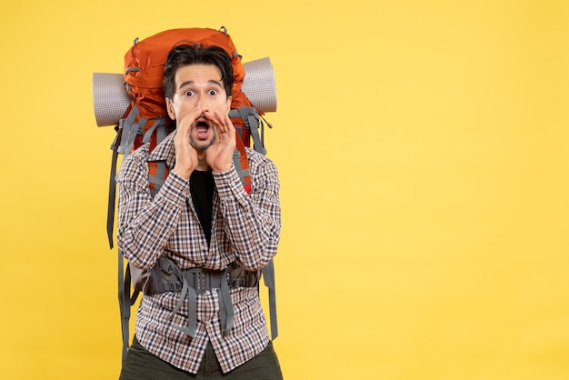 Vista frontale giovane maschio che va a fare un'escursione con lo zaino che chiama su sfondo giallo altezza turistica montagna colore campus umano